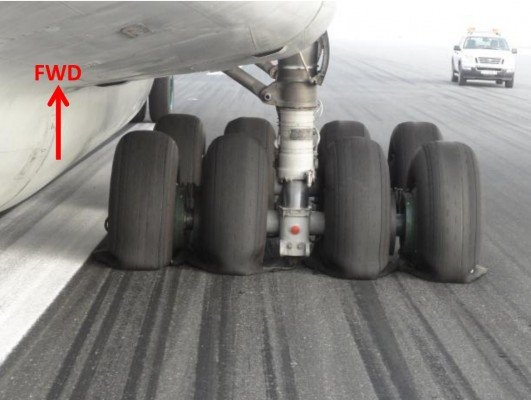 Il-76 right hand main gear with skid marks and deflated tyres (photo: GCAA)